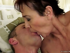 Brunette mature woman fucks a younger guy and gets facial